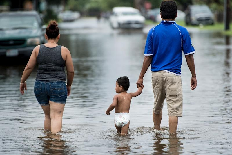 People walk through flooded streets in Galveston as heavy rains from Harvey leave a trail of destruction (AFP Photo/Brendan Smialowski)