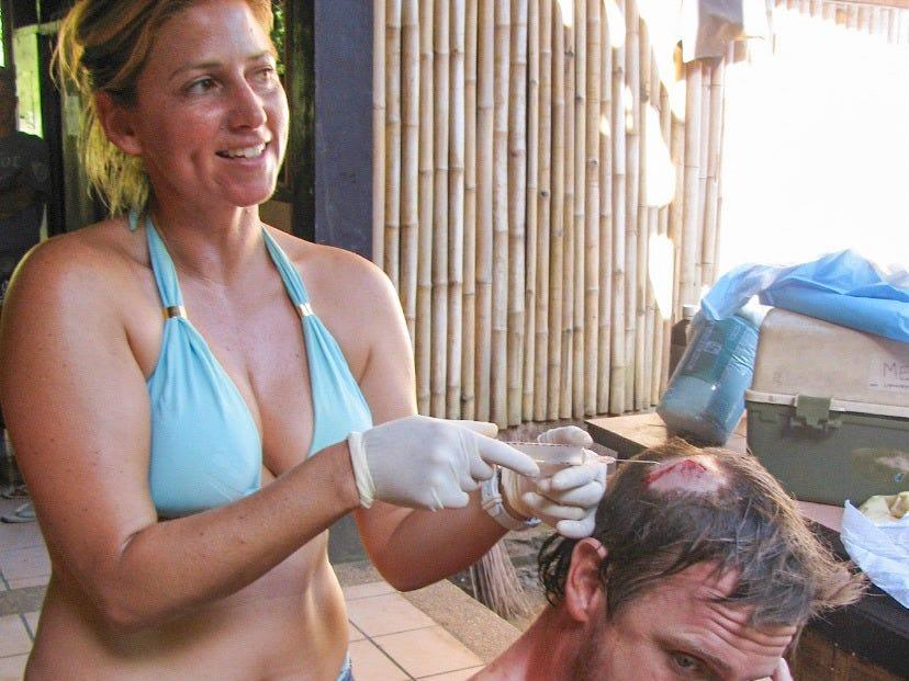 Myhre treats a patient's head wound while wearing a bikini.