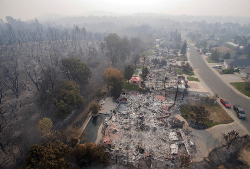 FILE - In this Aug. 10, 2018 file photo, homes destroyed by a wildfire are seen from an aerial view in the Mary Lake Subdivision in Redding, Calif. A financial tug-of-war is emerging over the $13.5 billion that Pacific Gas & Electric, the nation's largest utility, has agreed to pay to victims of recent California wildfires, as government agencies jockey for more than half the money to cover the costs of their response to the catastrophes. (AP Photo/Michael Burke, File)