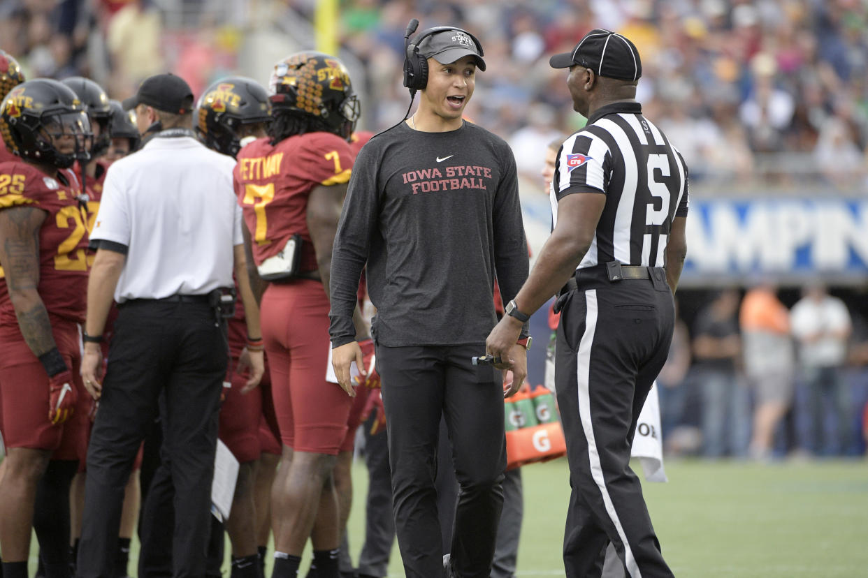 Iowa State wide receivers coach Nate Scheelhaase, center, talks to an official during a timeout in the first half of the Camping World Bowl NCAA college football game against Notre Dame Saturday, Dec. 28, 2019, in Orlando, Fla. (AP Photo/Phelan M. Ebenhack)