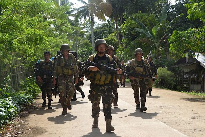 File Photo: Philippine soldiers walking along a highway as they return to camp at the village of Bongkaong, Patikul town, Sulu province on the southern island of Mindanao. (Photo: STRINGER/AFP via Getty Images)