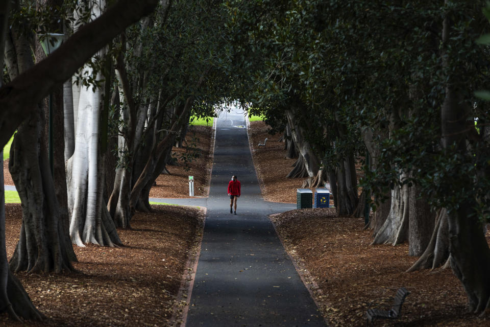 A man wearing a mask is seen walking in a Melbourne park as Melbourne goes into Stage 4 Lockdown due to the spread of COVID-19, Wednesday, Aug. 5, 2020. People are allowed to exercise for one hour a day within a 5-kilometer radius of their house. Victoria state, Australia's coronavirus hot spot, announced on Monday that businesses will be closed and scaled down in a bid to curb the spread of the virus. (AP Photo/Asanka Brendon Ratnayake)