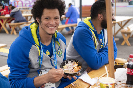 In this Aug. 3, 2019 photo, Thiagus Petrus, a member of the Brazilian handball team poses for photos while he takes a break from eating ceviche at the international center outside the Pan American athletes' village in Lima, Peru. Peruvian food was the star at the recent Pan Am Games. Athletes from 41 countries across the Americas tasted the highly-regarded cuisine that blends indigenous traditions with European, African and Asian influences with an abundance of seafood from the Pacific Oceans cold Humboldt current. (AP Photo/Luis Andres Henao)