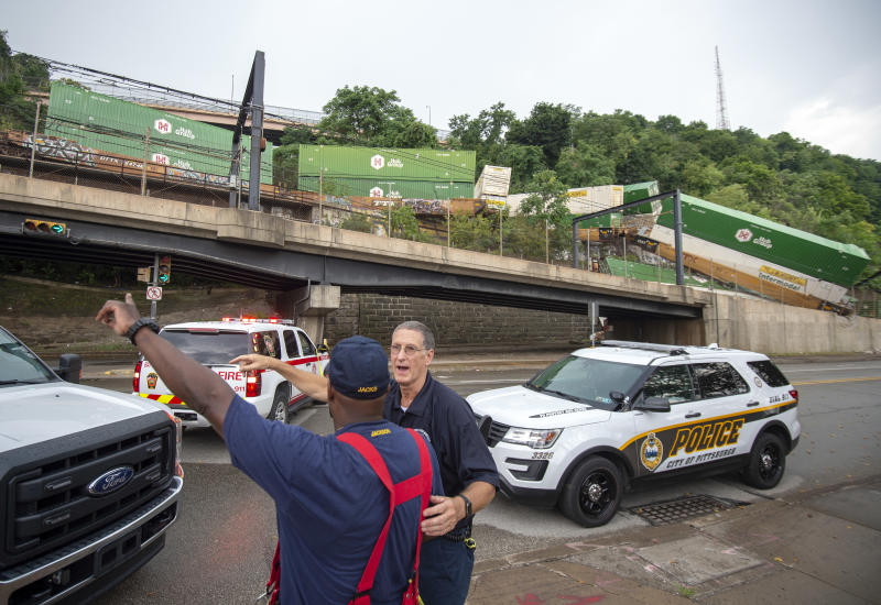 Emergency personnel work the scene of a train derailment above Carson Street on Sunday, Aug. 5, 2018, near Station Square in Pittsburgh. Four cars from a freight train derailed in Pittsburgh, sending containers tumbling down a hillside onto light rail tracks below, but no injuries have been reported, authorities said. (Steph Chambers/Pittsburgh Post-Gazette via AP)