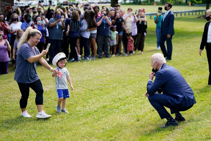 <p>Joe Biden stops outside at York High School in Virginia and is greeted by a child and his mother on 3 May.</p> (AP)