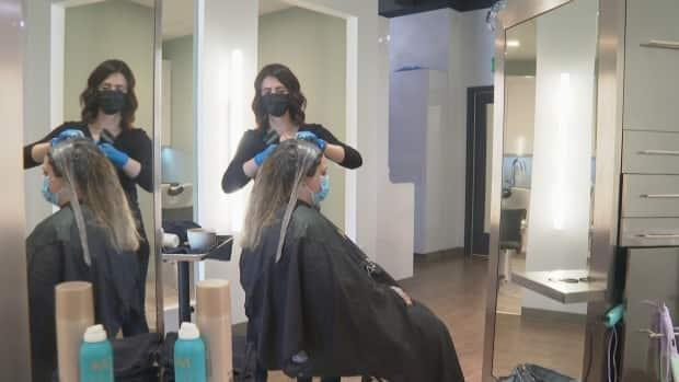 A stylist tends to a customer's hair at Vibrant Salon & Spa in Fredericton, which has changed its vaccination requirements twice already this week.   (Mrinali Anchan/CBC - image credit)
