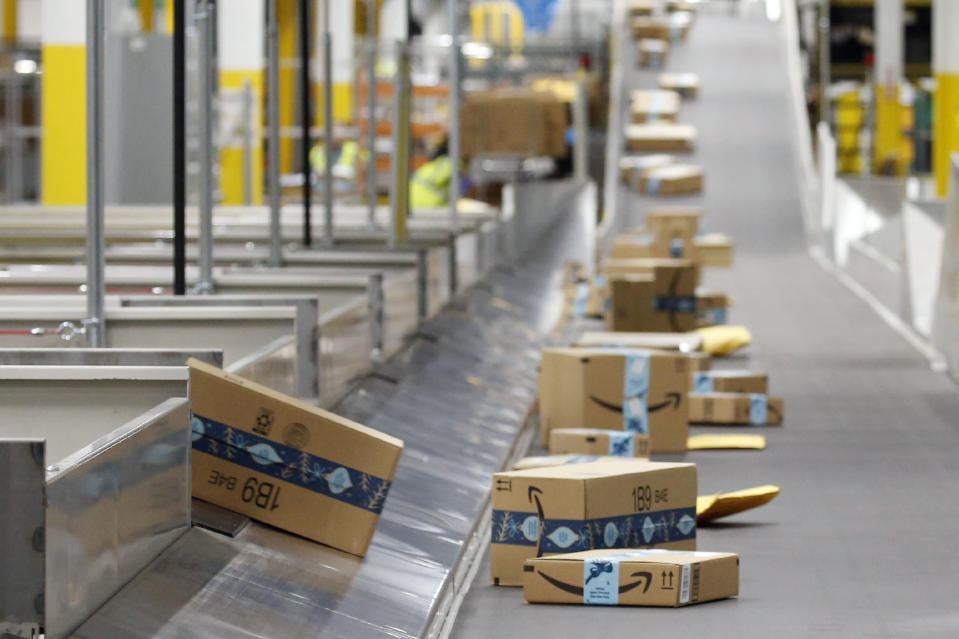 FILE - In this Dec. 17, 2019, file photo, Amazon packages move along a conveyor at an Amazon warehouse facility in Goodyear, Ariz. Amazon's pandemic boom isn't showing signs of slowing down. The company said Thursday, April 29, 2021, that its first-quarter profit more than tripled from a year ago, fueled by the growth of online shopping. It also posted revenue of more than $100 billion, the second quarter in row that the company has passed that milestone. (AP Photo/Ross D. Franklin, File)