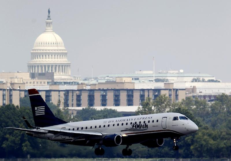 With the Capitol in the background, a US Airways airplane makes its final approach at Ronald Reagan Washington National Airport, Thursday, Aug. 2, 2012. Transportation Secretary Ray LaHood said Thursday that none of the three commuter jets that flew to close together near Washington was ever on course to collide head-on with the others.   (AP Photo/Haraz N. Ghanbari)