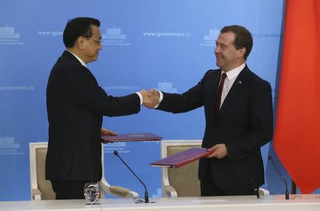 Russia's Prime Minister Dmitry Medvedev (R) shakes hands with China's Premier Li Keqiang during a signing ceremony in Moscow, October 13, 2014. REUTERS/Yekaterina Shtukina/RIA Novosti/Pool