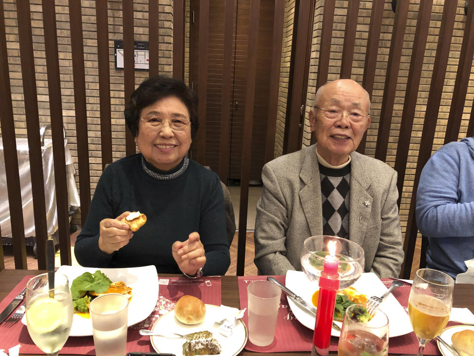 Shizue Akita, left, who died of COVID-19 at an Osaka hospital on May 13, 2021, and her husband Yukihiko Akita smile at Yukihiko's birthday party in Tondabayashi, western Japan, November 2019. As she struggled to breathe, Shizue Akita had to wait more than six hours while paramedics searched for a hospital in Osaka that would treat her worsening COVID-19. When she finally got to one that wasn't overwhelmed with other patients, doctors diagnosed severe pneumonia and organ failure and sedated her. Akita, 87, was dead two weeks later. (Kazuyuki Akita via AP)