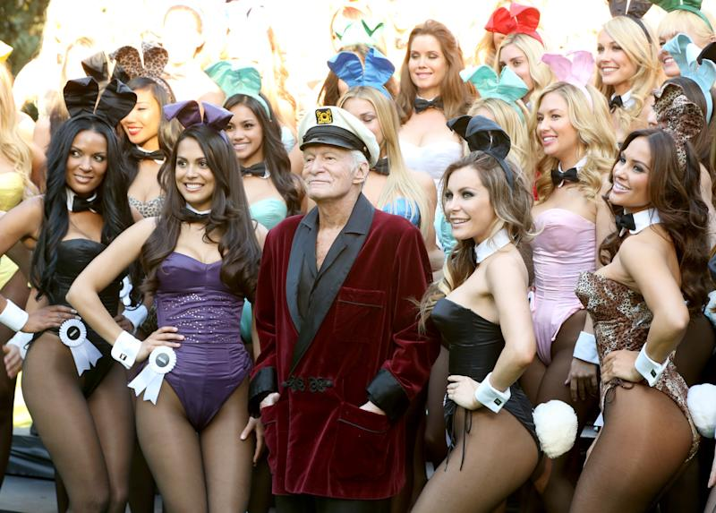 Hugh Hefner is surrounded by Playboy Bunnies and is flanked by Playmate of the Year 2013 Raquel Pomplun (left) and his wife, Crystal, at a 60th anniversary event on Jan. 16, 2014, in Los Angeles. (Rachel Murray via Getty Images)
