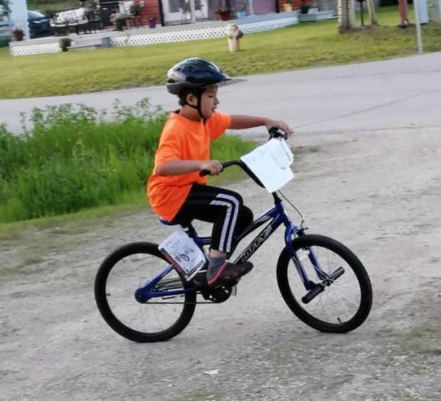 Oliver, Ming Sun's son, rides his new bike in Fort Smith, N.W.T. (Submitted by Ming Sun - image credit)