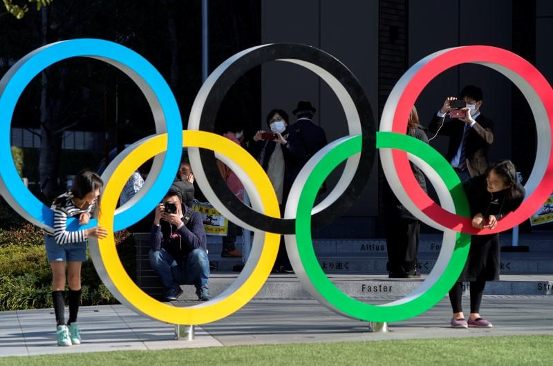 Visitors wearing protective face masks following an outbreak of the coronavirus disease are seen through the Olympic rings in Tokyo