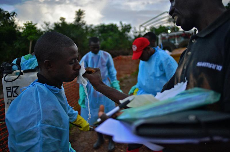 Sierra Leonese government burial team members are disinfected after loading the bodies of Ebola victims onto a truck in Kailahun, on August 14, 2014 (AFP Photo/Carl de Souza)