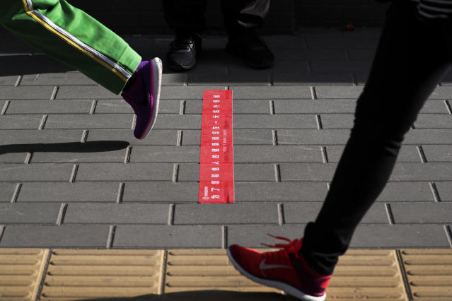 Students walk past a sticker to remind students to keep their social distancing as they arrive for the reopening of a primary school in Beijing, Monday, June 1, 2020. With declining virus case numbers, students have gradually returning to their classes in the capital city. (AP Photo/Andy Wong)