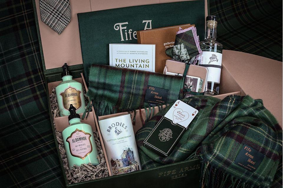 """<p>No hotel in the world does a hamper quite like the Fife Arms. The Scottish mainstay is known throughout the world for its impressive art collection that includes Picasso and Freud. Carefully curated with gentlemen in mind, the Flying Stag hamper features some of the retreat's most beloved keepsakes, including a delightfully soft Fife Arms tartan lambswool blanket, a tartan cashmere scarf, a bottle of Flying Stag gin, a tweed pocket tie, a pocket square and playing cards. He will love it. </p><p>£690, <a href=""""https://shop.thefifearms.com/collections/shop-all-collection/products/the-flying-stag-hamper"""" rel=""""nofollow noopener"""" target=""""_blank"""" data-ylk=""""slk:the Fife Arms"""" class=""""link rapid-noclick-resp"""">the Fife Arms</a>.</p>"""