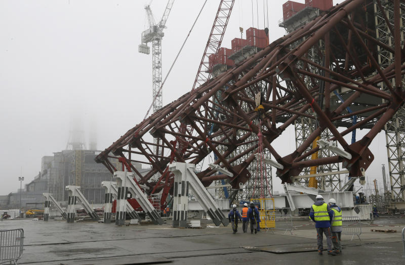 Construction workers assist in the assembly of a gigantic steel-arch to cover the remnants of the exploded reactor at the Chernobyl nuclear power plant in Chernobyl, Ukraine, Tuesday, Nov. 27, 2012. The new safe confinement, a structure that is being built over reactor 4 damaged in 1986 as a result of the world's worst nuclear accident, will cover a hastily built sarcophagus, which was erected shortly after the explosion. (AP Photo/ Efrem Lukatsky)