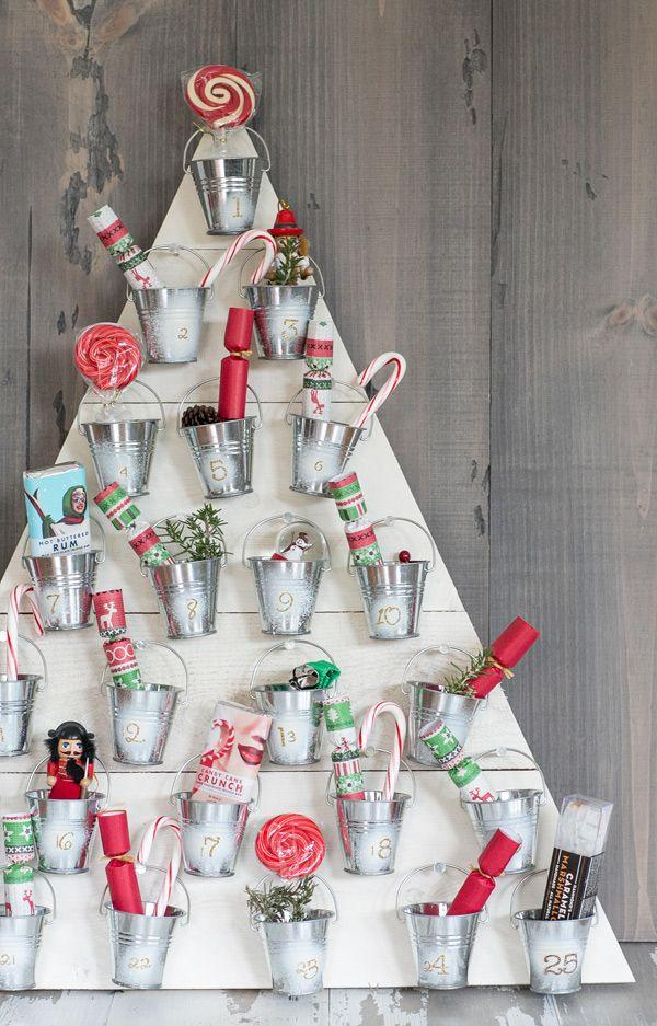 "<p>Here's another great DIY advent calendar brought to us by <a href=""https://sugarandcharm.com/diy-wooden-advent-calender"" target=""_blank"">Sugar and Charm</a>. You'll just need some plywood, small tin cans, and a hot glue gun (and then goodies, of course).</p>"