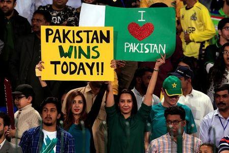 Pakistani spectators hold placards at Gaddafi Cricket Stadium as they wait for the start of a hugely anticipated finals of its domestic cricket league, Pakistan Super League (PSL) in Lahore, Pakistan, March 5, 2017. REUTERS/Faisal Mahmood