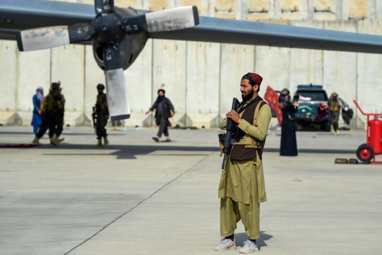 Taliban fighters stand guard near an Afghan Air Force aircraft at the airport in Kabul on August 31, 2021, after the US pulled all its troops out of the country (AFP/Wakil KOHSAR)