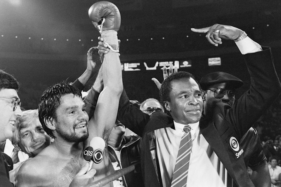 Sportscaster and former welterweight champion Sugar Ray Leonard holds up the arm and points at boxer Robert Duran after Duran defeated Davey Moore to win the WBC Junior Middleweight crown. New York, June 17, 1983.