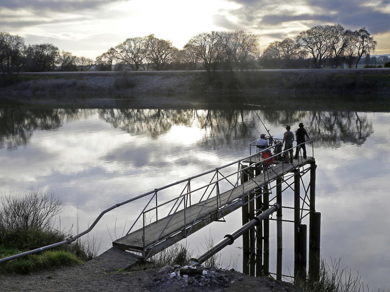 """FILE - In this Feb. 23, 2016 file photo, people try to catch fish along the Sacramento River in the San Joaquin-Sacramento River Delta, near Courtland, Calif. California officials sued the Trump administration on Thursday, Feb. 20, 2020, to block new rules governing the Sacramento/San Joaquin River Delta. Attorney General Xavier Becerra called the new rules """"scientifically challenged"""" and said they would push some species to extinction. (AP Photo/Rich Pedroncelli, File)"""