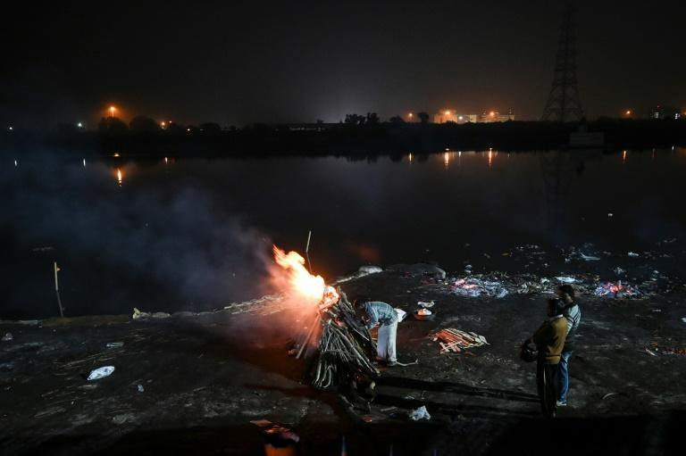 A man lights up a funeral pyre for a friend who died in this week's Delhi riots