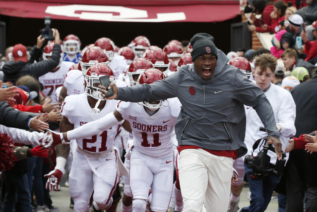 Former Oklahoma player Adrian Peterson leads the white team onto the field as an honorary coach for the Oklahoma NCAA college football spring intra-squad game in Norman, Okla., Saturday, April 14, 2018. (AP Photo/Sue Ogrocki)