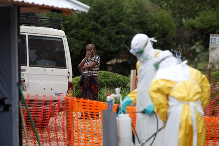 A woman waits next to an ambulance carrying a suspected Ebola patient at an Ebola transit centre in town of Katwa near the Eastern Congolese town of Butembo