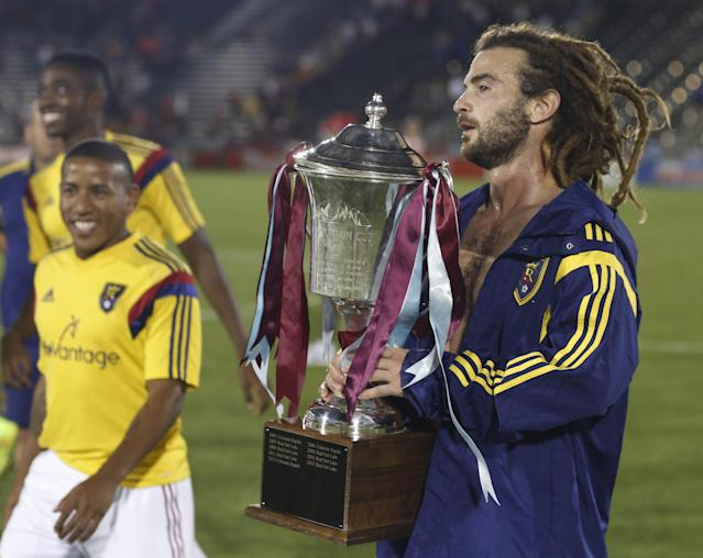 As his teammates look on, Real Salt Lake midfielder and captain Kyle Beckerman carries the Rocky Mountain Cup after the team's 1-0 victory over the Colorado Rapids in a soccer game in Commerce City, Colo., on Saturday, Aug. 2, 2014. With the win, Real Salt Lake claimed the Rocky Mountain Cup, which is awarded to the winner of the teams' regular-season schedule. (AP Photo/David Zalubowski)