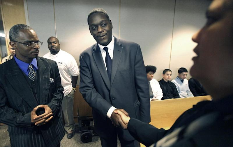 "In this photo made Wednesday, Feb. 22, 2012, Dallas County District Attorney Craig Watkins, center, shakes hands with attorney Cheryl Watley, right, as Richard Miles looks on in a courtroom in Dallas. Watkins, whose office has freed more than 20 wrongfully convicted inmates, questioned whether Texas has executed an innocent person and called for a statewide ""conversation"" about how capital punishment is administered. Watkins described himself as a moral opponent of the death penalty who has pursued it in several cases because it's the law. He also talks for the first time about his great-grandfather, who was executed in 1932 after being convicted of murder and robbery. Watkins says that dark chapter in his family's history made him more aware of what needs to be changed. (AP Photo/LM Otero)"