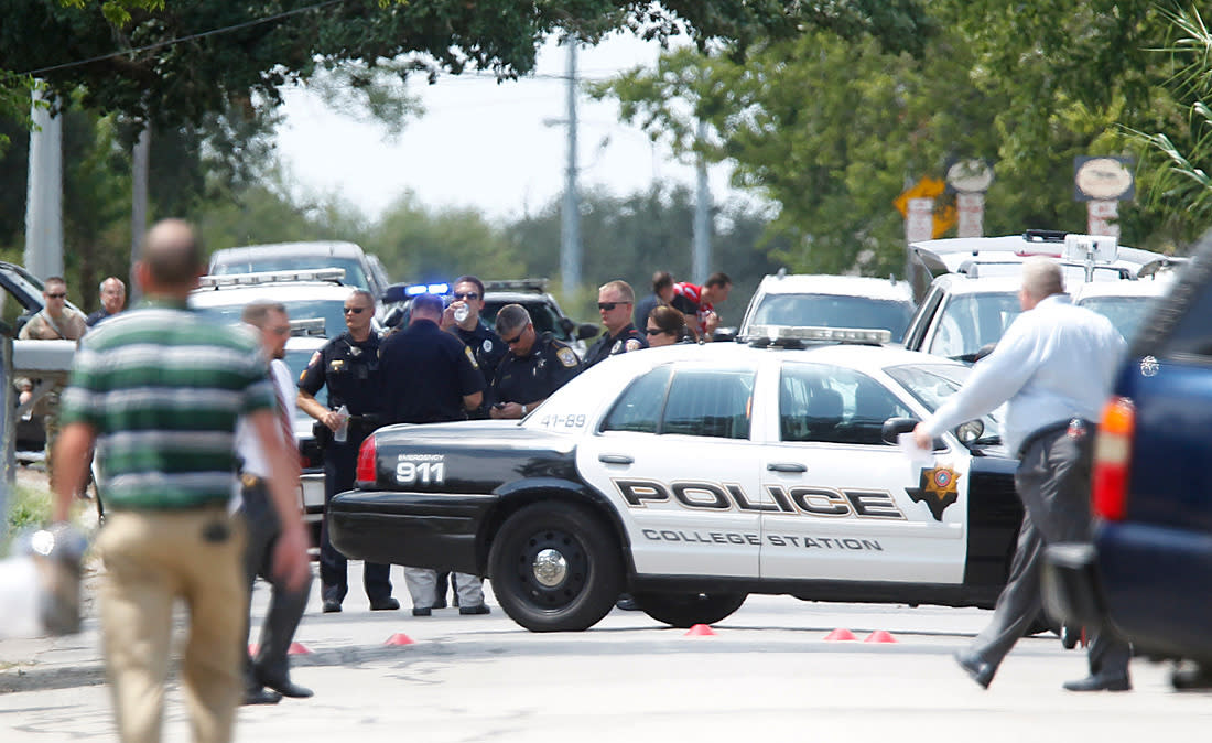 Police gather near the scene where a gunman opened fire on a police officer serving an eviction notice near the Texas A&M University on Monday, Aug. 13, 2012, in College Station, Texas. College Station Assistant Police Chief Scott McCollum says Brazos County Constable Brian Bachmann was among three people, including the gunman, killed in the shootout. (AP Photo/Houston Chronicle, Mayra Beltran) MANDATORY CREDIT: NO SALES, MAGS OUT, TV OUT, INTERNET: AP MEMBERS ONLY
