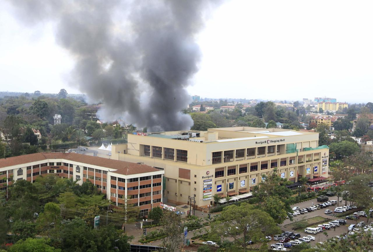 Smoke rises from the Westgate shopping centre after explosions at the mall in Nairobi September 23, 2013. Thick smoke poured from the besieged Nairobi mall where Kenyan officials said their forces were closing in on Islamists holding hostages on Monday, three days after a raid by Somalia's al Shabaab killed at least 62 people. It remained unclear how many gunmen and hostages were still cornered in the Westgate shopping centre, two hours after a series of loud explosions and gunfire were followed by a plume of black smoke, that grew in volume from one part of the complex. REUTERS/Noor Khamis (KENYA - Tags: CIVIL UNREST POLITICS TPX IMAGES OF THE DAY)