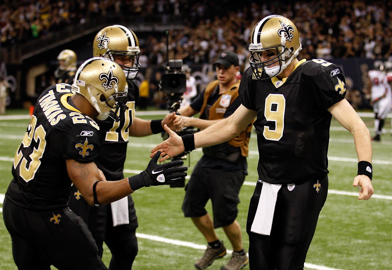 NEW ORLEANS, LA - DECEMBER 26:  (R) Quarterback Drew Brees #9 of the New Orleans Saints celebrates throwing a 24-yard third quarter touchdown pass with running back Pierre Thomas #23 and quarterback Chase Daniel #10 against the Atlanta Falcons at the Mercedes-Benz Superdome on December 26, 2011 in New Orleans, Louisiana.  (Photo by Chris Graythen/Getty Images)