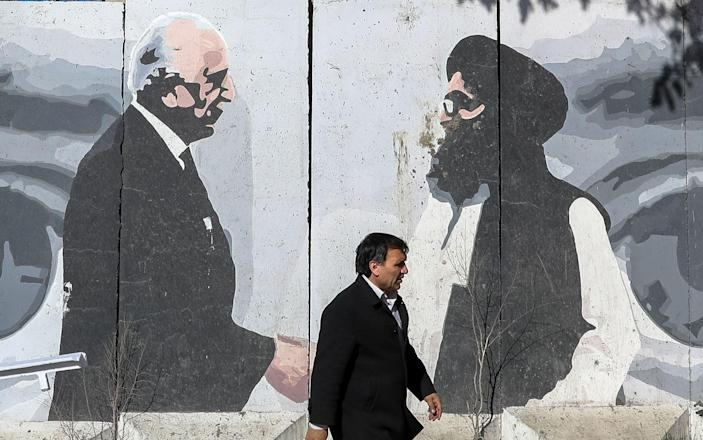 Afghan man passes by a wall painted with a photo of Zalmay Khalilzad, U.S. special envoy in Afghanistan (L), and Mullah Abdul Ghani Baradar, the leader of the Taliban delegation - Shutterstock