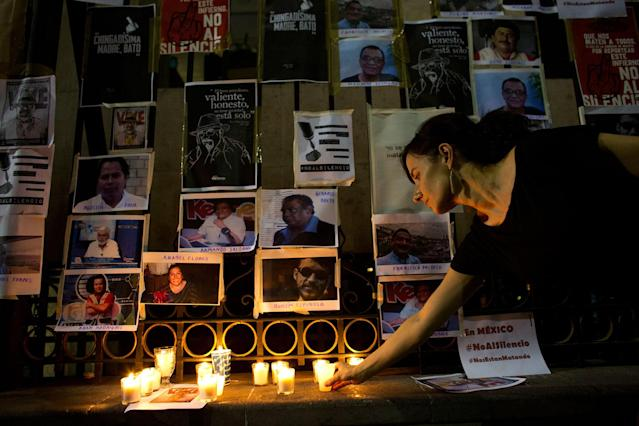 <p>A woman lays a candle in front of pictures of murdered journalists taped to a fence surrounding the Interior Ministry in Mexico City, Tuesday, May 16, 2017. (AP Photo/Rebecca Blackwell) </p>