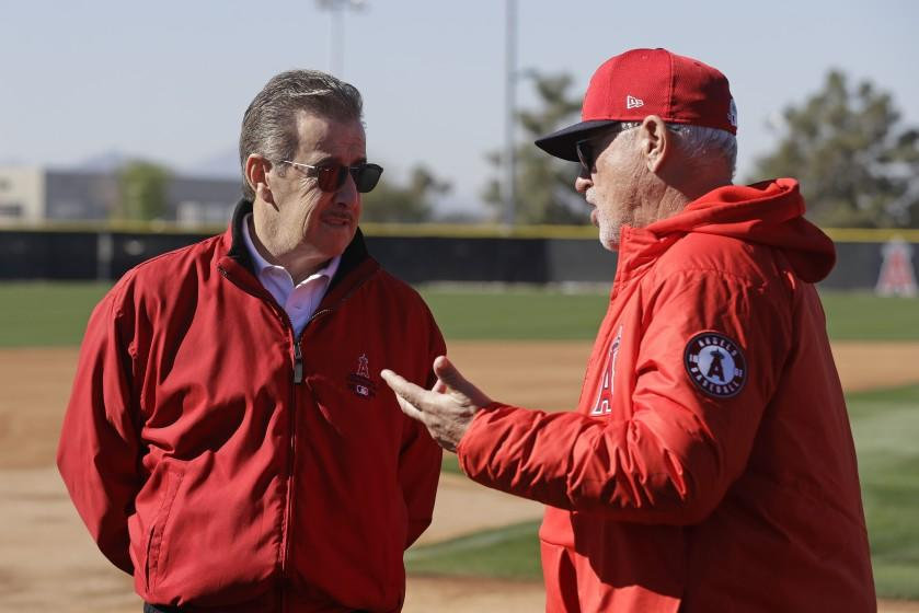 Los Angeles Angels manager Joe Maddon, right, talks with Los Angeles Angels owner Arte Moreno during spring training baseball practice, Wednesday, Feb. 12, 2020, in Tempe, Ariz. (AP Photo/Darron Cummings)