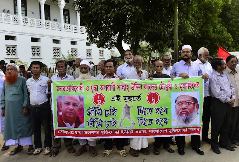 Bangladeshi freedom fighters who fought in the 1971 war of indepence with Pakistan hold a banner with images of Salauddin Quader Chowdhury (L) and Ali Ahsan Mohammad Mujahid (R), in Dhaka on November 2, 2015 (AFP Photo/Munir Uz Zaman)