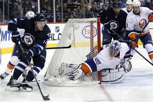 New York Islanders' goaltender Evgeni Nabokov (20) tries to poke check Winnipeg Jets' James Wright (17) as he comes around the net during second period of an NHL game in Winnipeg, Manitoba, Saturday, April 20, 2013. (AP Photo/The Canadian Press, John Woods)