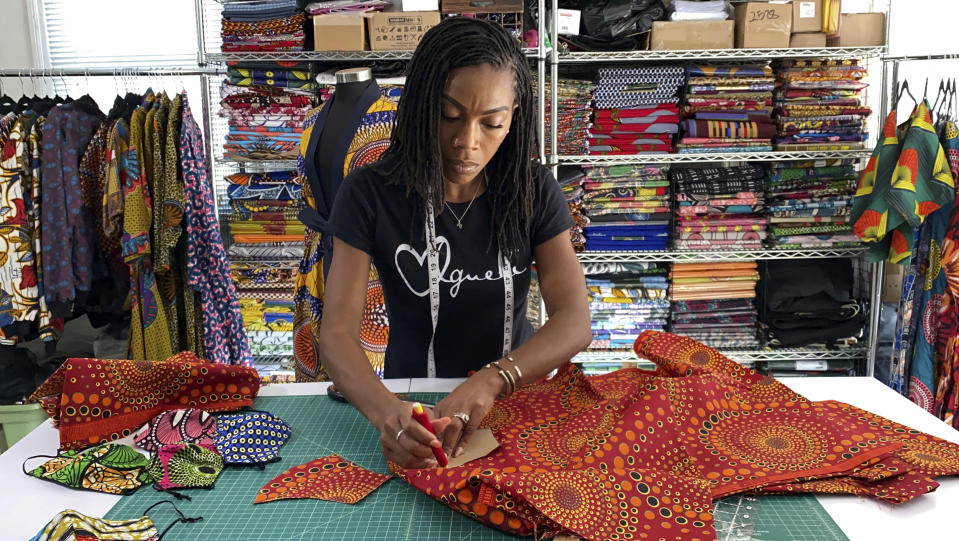 """Iguehi James, an Oakland, Calif., fashion entrepreneur, cuts fabric to make a face mask she sells through her apparel company Love Iguehi, Tuesday, Sept. 15, 2020. She received a $5,000 grant from the Oakland African American Chamber of Commerce's """"Resiliency Fund,"""" which seeks to help Black-owned businesses stay afloat during the coronavirus pandemic. (AP Photo/Terry Chea)"""