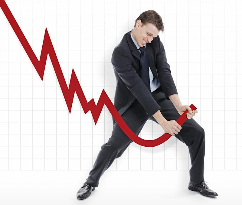 A businessman turning a red, downward pointing arrow upwards.