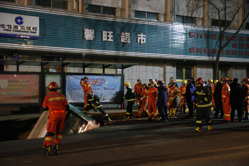 In this photo taken Monday, Jan. 13, 2020, firefighters descend into a chasm that opened up and swallowed a bus in Xining in northwestern China's Qinghai province. The bus plunged through a collapsed section of road in northwestern China, killing some and leaving others missing, authorities said. (Ma Minyan/cnsphoto via AP)