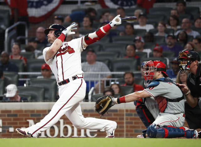 Atlanta Braves third baseman Josh Donaldson (20) follows through on a home run in front of Philadelphia Phillies catcher J.T. Realmuto (10) during the fourth inning of a baseball game Thursday, July 4, 2019, in Atlanta. (AP Photo/John Bazemore)