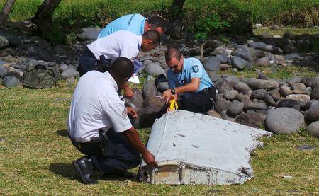 File picture shows French gendarmes and police inspecting a large piece of plane debris which was found on the beach in Saint-Andre on the French Indian Ocean island of La Reunion