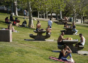 """People enjoy the sunny weather at Pan Pacific Park in the Fairfax District of Los Angeles, Thursday, April 8, 2021. California Gov. Gavin Newsom announced Tuesday, April 6, that the state of nearly 40 million will lift most pandemic restrictions June 15 provided hospitalization rates stay low and there is enough vaccine for everyone. It's unclear if the drop in supply will affect California's reopening date, although the governor's office said on social media that """"CA is on track to open safely 6/15."""" (AP Photo/Damian Dovarganes)"""