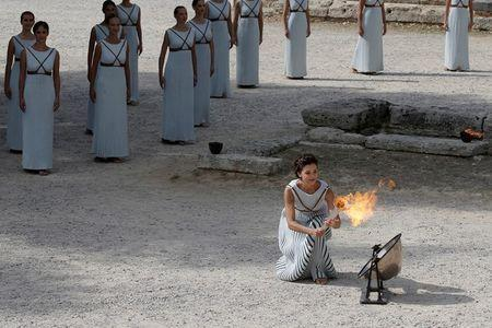 Olympics - Dress Rehearsal - Lighting Ceremony of the Olympic Flame Pyeongchang 2018 - Ancient Olympia, Olympia, Greece - October 23, 2017 Greek actress Katerina Lehou, playing the role of High Priestess, lights a torch from the sun's rays reflected in a parabolic mirror during the dress rehearsal for the Olympic flame lighting ceremony for the Pyeongchang 2018 Winter Olympic Games at the site of ancient Olympia in Greece REUTERS/Costas Baltas