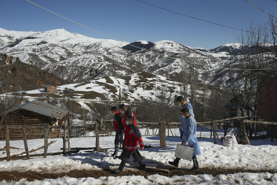 Doctors and health workers of a COVID-19 vaccination team, walk in the isolated village of Gumuslu in the district of Sivas, central Turkey, Friday, Feb. 26, 2021. After traveling snow and ice covered roads, medical workers arrived in the small settlement of 350 people some 140 miles (230 kilometers) from the provincial capital, to vaccinate older villagers. (AP Photo/Emrah Gurel)