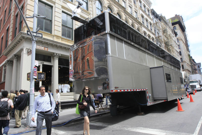 "Pedestrians walk on the corner of Broome and Greene Streets next to a double-decker movie trailer parked in the Soho neighborhood in the Manhattan borough of New York, Wednesday, May 11, 2011.  The trailer, for Will Smith's movie ""Men in Black III,""  is causing complaints from area residents. (AP Photo/Mary Altaffer)"