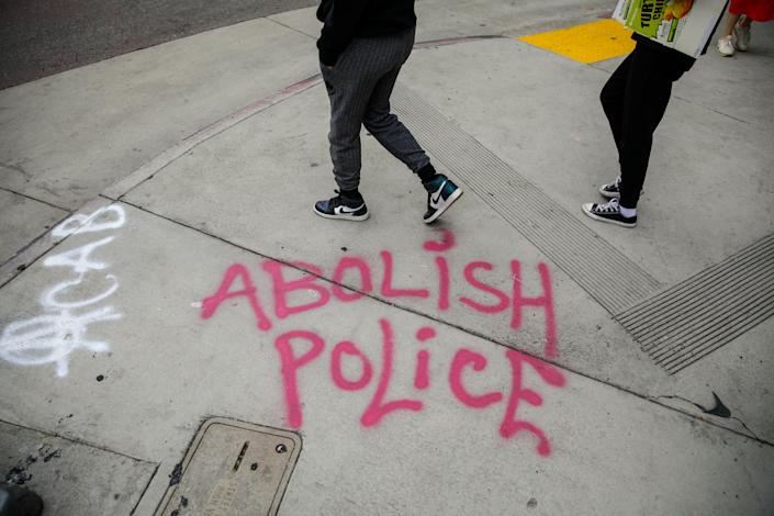 The words Abolish Police is spray painted on the sidewalk as about 1,000 people gathered to protest the death of George Floyd and in support of Black Lives Matter, in downtown, Los Angeles, CA, on Friday, June 5, 2020. (Jay L. Clendenin/Los Angeles Times via Getty Images)