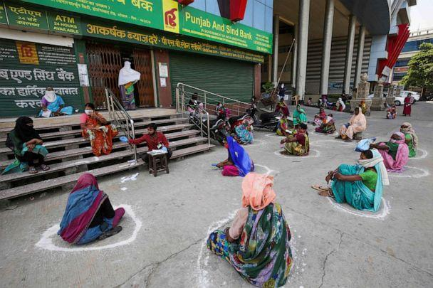 PHOTO: Women maintain social distancing outside a bank as they wait to collect their pension during a government-imposed nationwide lockdown as a preventive measure against the spread of the novel coronavirus in Bhopal, India, on April 15, 2020. (Gagan Nayar/AFP via Getty Images)